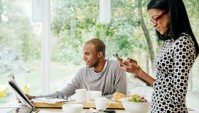 Mid-adult heterosexual couple eating breakfast, Reading newspaper and text messaging